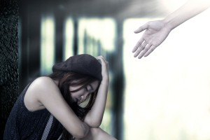 Hand reaching out to depressed girl