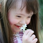 Down syndrome girl smells flower