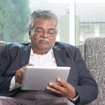 Older man on tablet reading