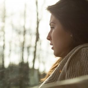 Sad woman looks out window