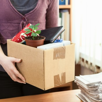 Woman holds box full of desk contents