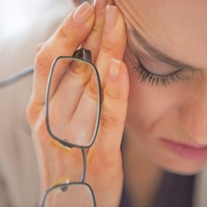 woman holding glasses, looking down sadly